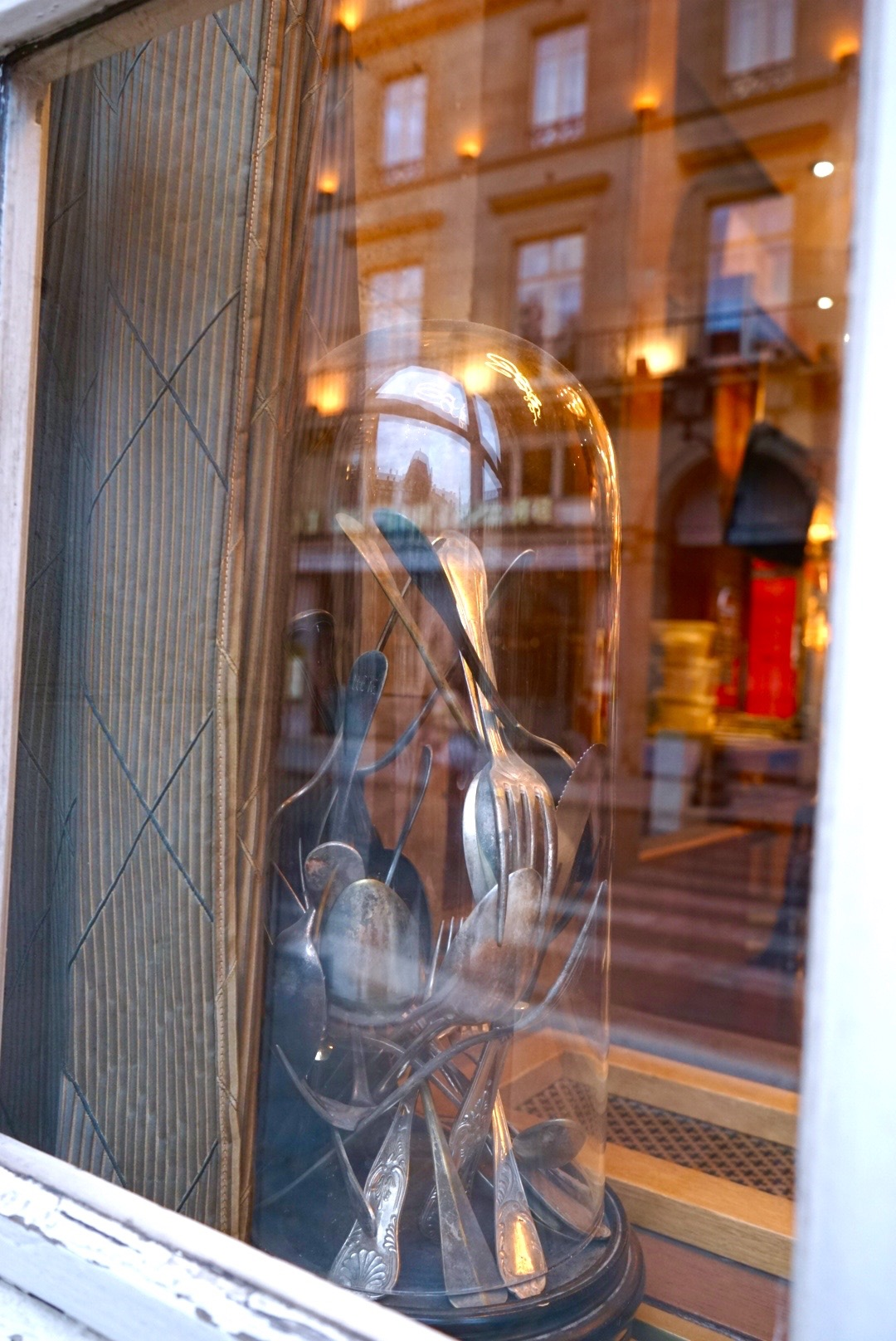 Paris ~ cloche filled with flatware sculpture in window sill of coffee shop